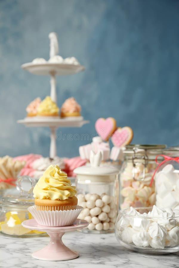 Godisstången med olika sötsaker på vit marmorerar tabellen mot färgbakgrund arkivfoton