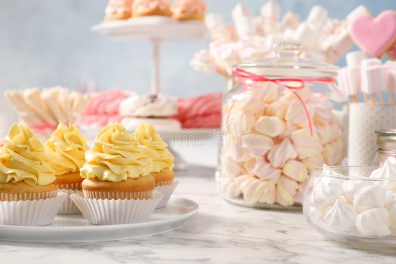 Godisstången med olika sötsaker på vit marmorerar tabellen arkivbild