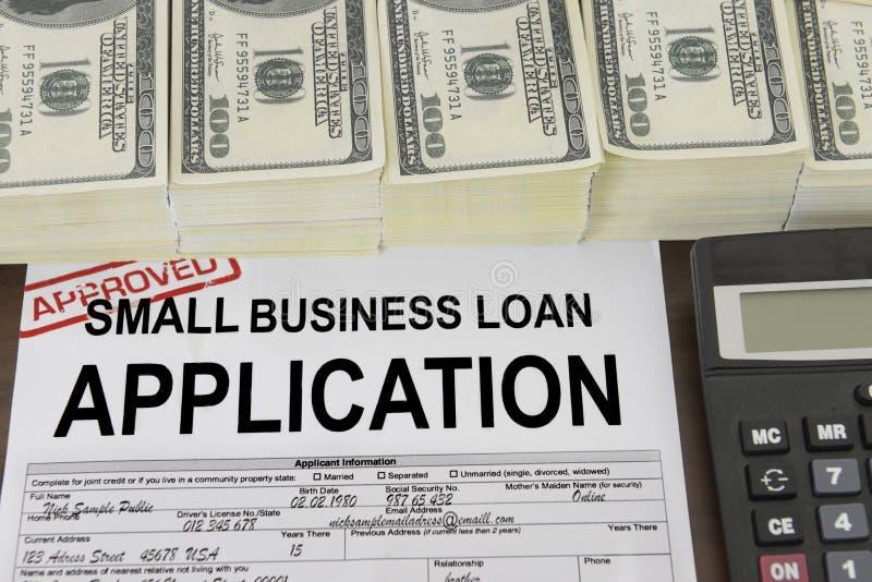 Godkänd lånansökningsblankett och pengar för liten affär royaltyfria bilder