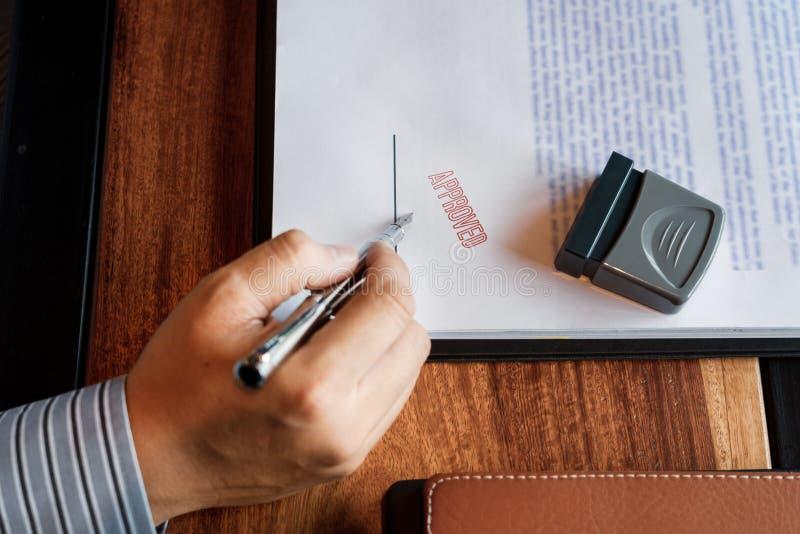 Godkänner det sättande eller undertecknande häftet för den höga handen för affärsmannen manliga i certifikatavtalet efter stämpel royaltyfri foto