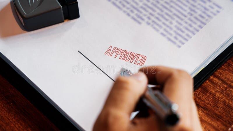 Godkänner det sättande eller undertecknande häftet för den höga handen för affärsmannen manliga i certifikatavtalet efter stämpel arkivfoton
