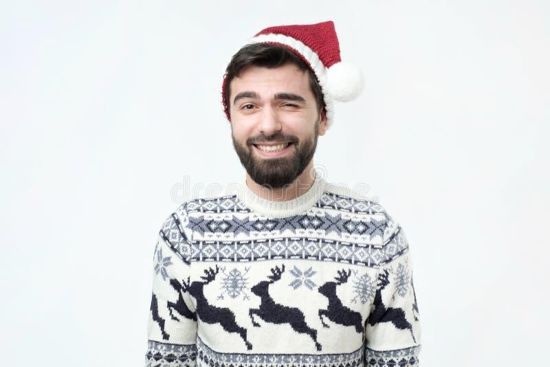 Godsdienstig vrolijk Spaans mannetje in rode Kerstmishoed met gelukkige uitdrukking royalty-vrije stock afbeelding