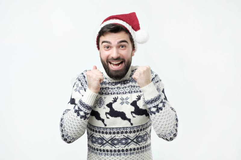Godsdienstig vrolijk Spaans mannetje in rode Kerstmishoed met gelukkige uitdrukking stock foto's