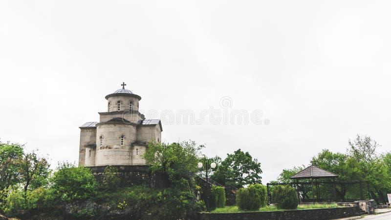 Godsdienstige architectuur Koepel van Servische Orthodoxe Kerk onder Ostrog-Klooster in Montenegro stock afbeeldingen