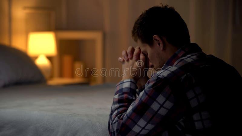 Godsdienstige jonge mens die in avond dichtbij bed, overtuiging in God bidden, Christendom stock foto's