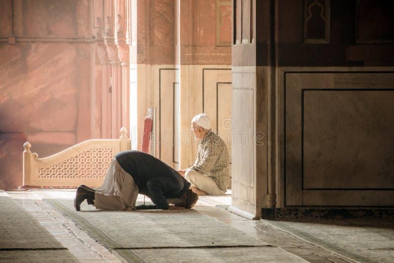 Godsdienstige moslimmens die binnen de moskee bidden Twee oudere Moslims bij de grote Vrijdagmoskee Jami Masjid in New Delhi, Ind stock fotografie