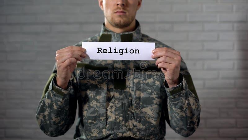 Godsdienstwoord op teken in handen van mannelijke militair, geloof in God wordt geschreven, gebed dat royalty-vrije stock foto's