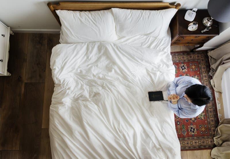Godsvruchtige vrouw met een bijbelboek die door het bed bidden stock afbeelding