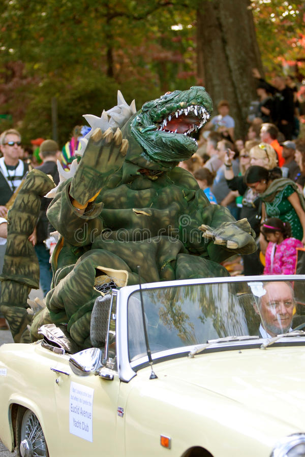 Godzilla Waves To Crowd In Halloween Parade. Atlanta, GA, USA - October 20, 2012: Godzilla character waves to crowd while riding in a convertible in the Little royalty free stock images