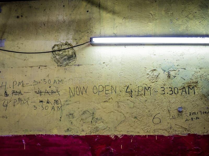 Godziny Otwarcia na ścianie z Fluorescencyjnym światłem zdjęcie stock