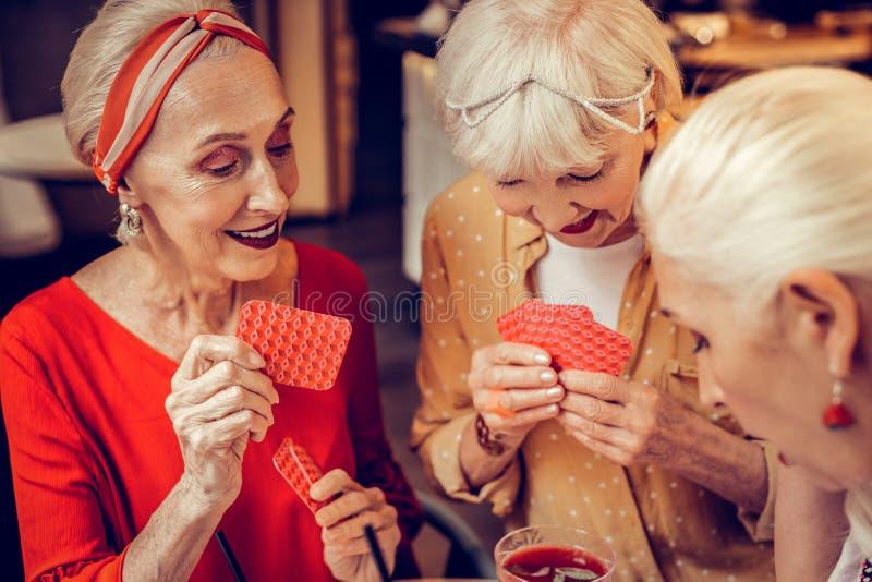 Goed-gehandhaafde modieuze hogere dames die van kaartspel genieten royalty-vrije stock foto's