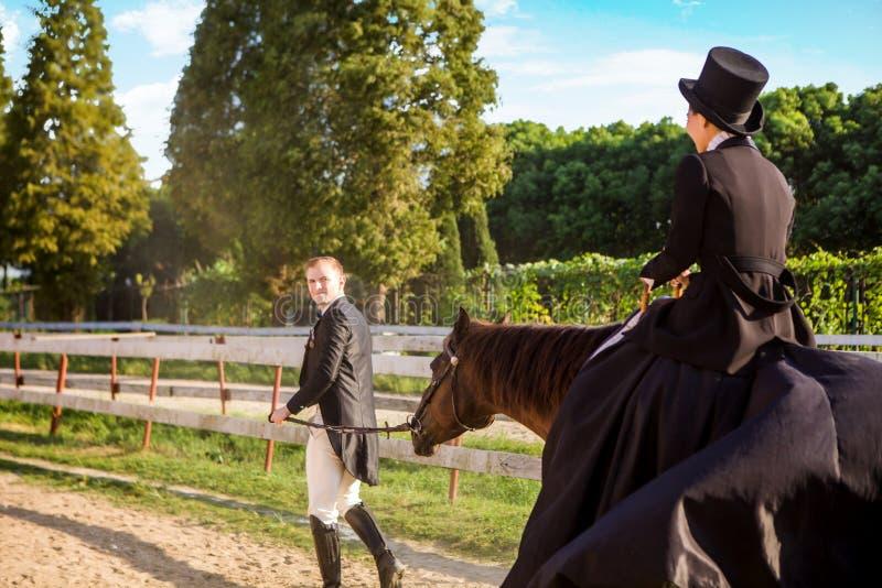 Goed-geklede man die vrouwenzitting op paard trekken bij gebied royalty-vrije stock foto