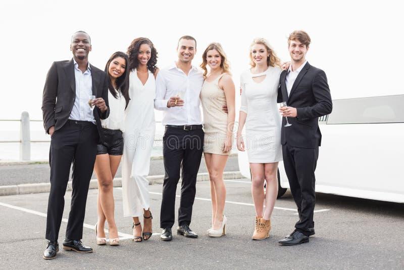 Goed geklede mensen die naast een limousine stellen royalty-vrije stock foto