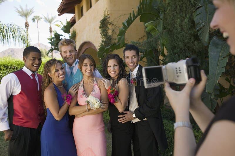 Goed-geklede tieners die voor videocamera buiten schooldans stellen stock foto's