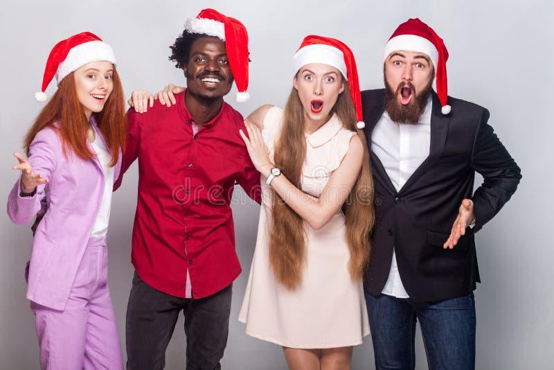 Goed geklede verbaasde arbeiders die in Kerstmishoed camera w bekijken stock fotografie