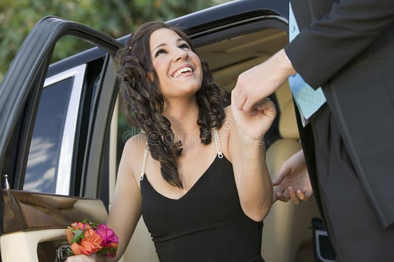 Goed-gekleed tienermeisje die uit limo door datum worden geholpen stock afbeelding