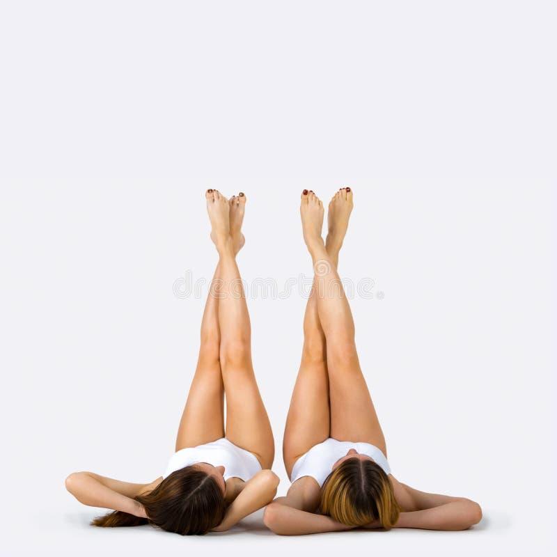 Goed gevormde vrouwelijke benen Portret van twee mooie jonge vrouwen stock foto's
