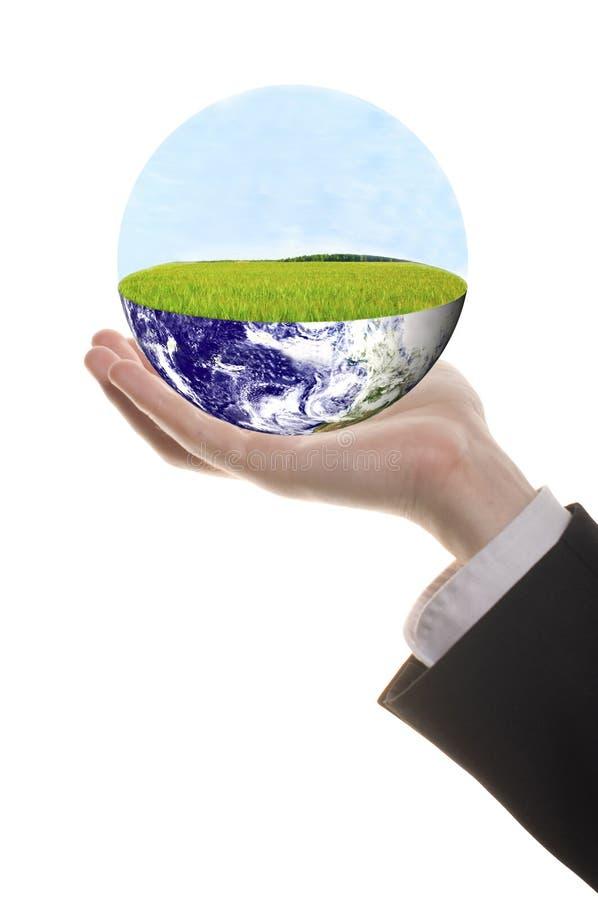 Goed gevormde zakenmanhand met groene aarde stock foto