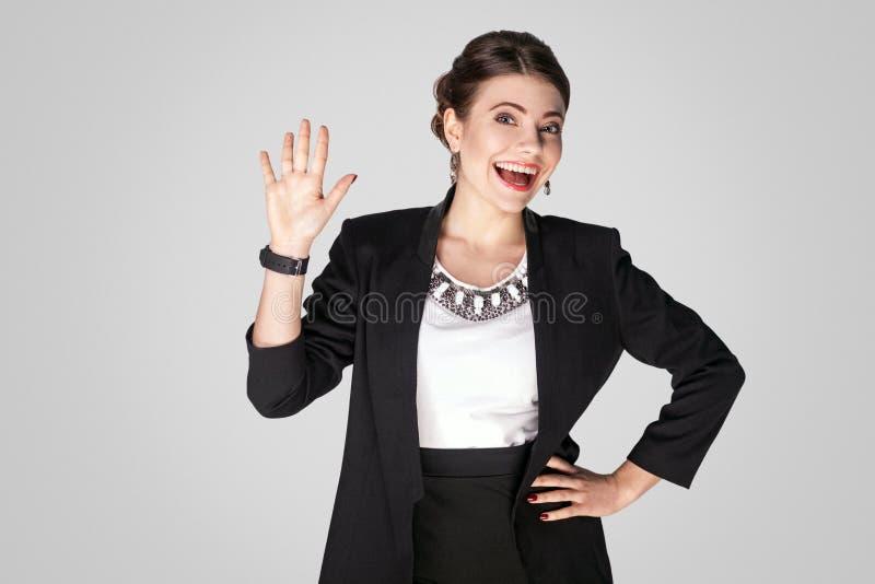 Goed hallo! Vrouw in kostuum die camera bekijken en hello teken tonen royalty-vrije stock afbeelding