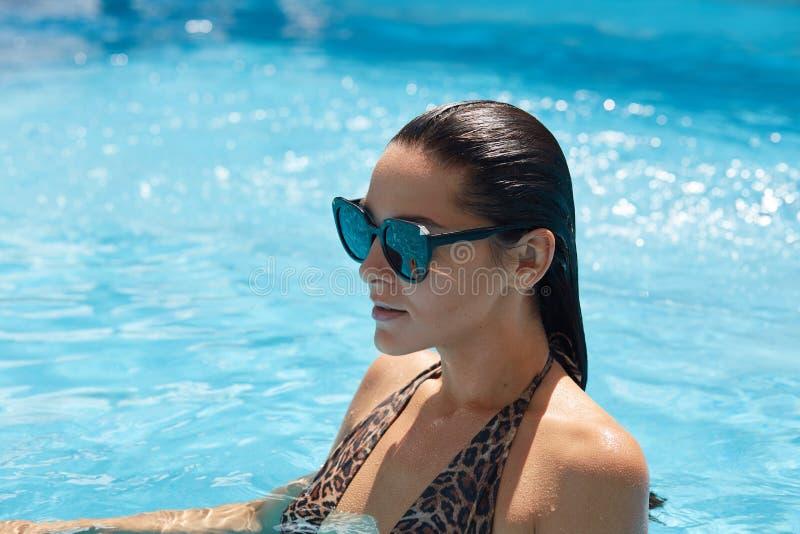 Goed het gelooide mooie vrouwelijke past stellen in water, die het zwemmen dragen en in zonnebril aan, die in zwembad, het geniet royalty-vrije stock afbeeldingen