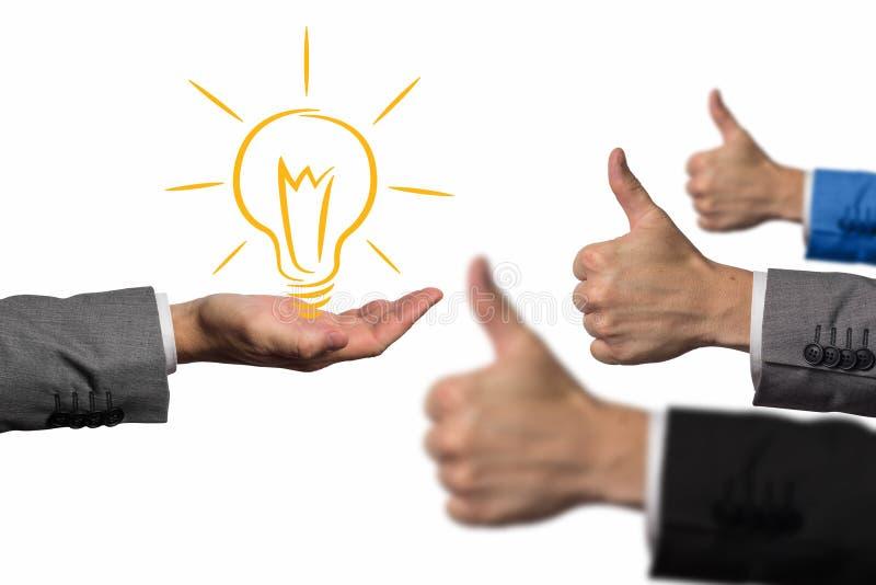 Goed ideeconcept Hand die een lightbulb houden terwijl andere handen die duimen op handteken tonen Het concept van het zakenmanid royalty-vrije stock fotografie