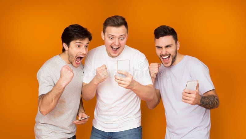 Goed Nieuws Opgetogen vrienden die mobiele telefoons houden stock afbeelding