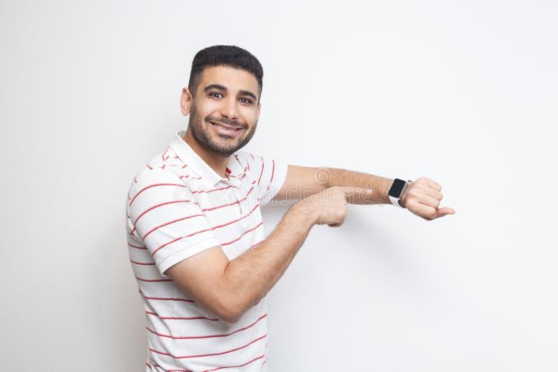 Goed resultaat en ontime Gelukkige knappe gebaarde jonge mens in gestreepte t-shirt die, zijn slim horloge tonen en bekijken bij  royalty-vrije stock afbeelding