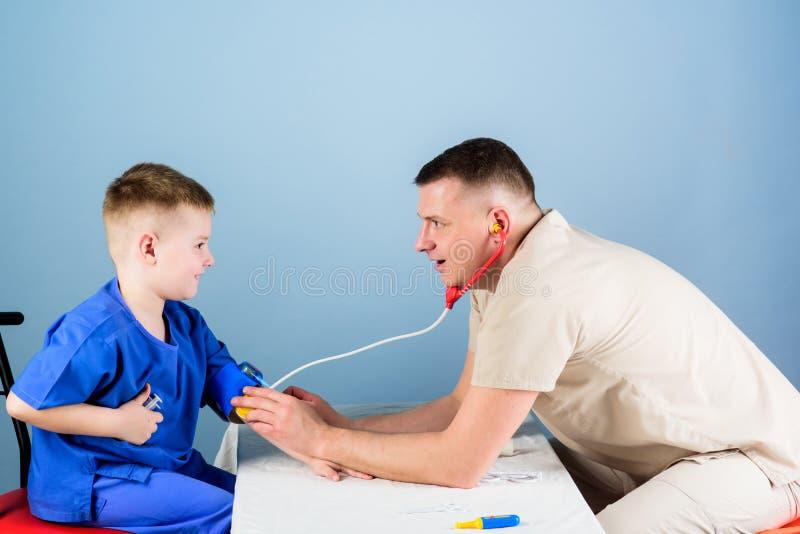 Goed team gelukkig kind met vader met stethoscoop de medewerker van het verpleegsterslaboratorium Huisarts vader en zoon binnen royalty-vrije stock foto's