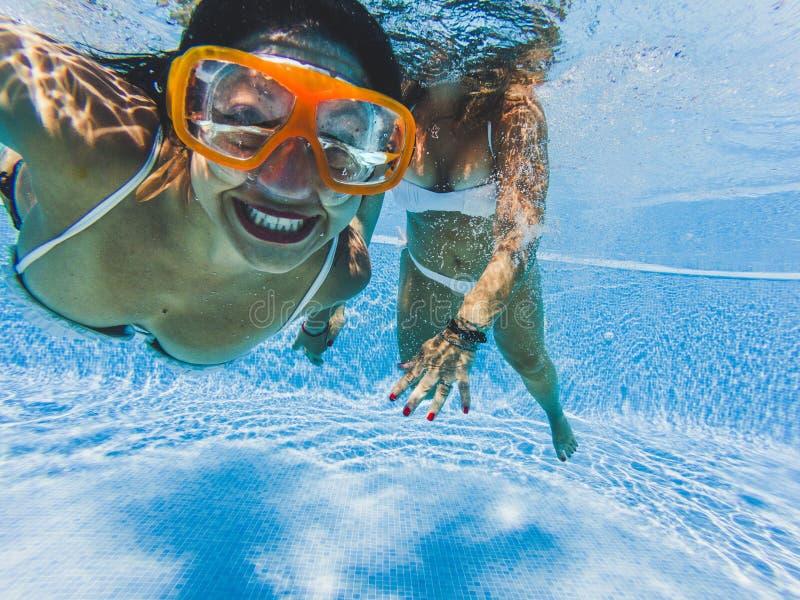 Goedaardige gelukkige mensen die een caucasisch meisje glimlachte onder water met een vriend - reis en speel samen in het blauwe w stock afbeeldingen