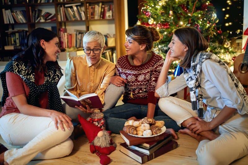Goedaardige oma en haar kleindochter samen voor Kerstmis voor een versierde x-mas boom stock foto