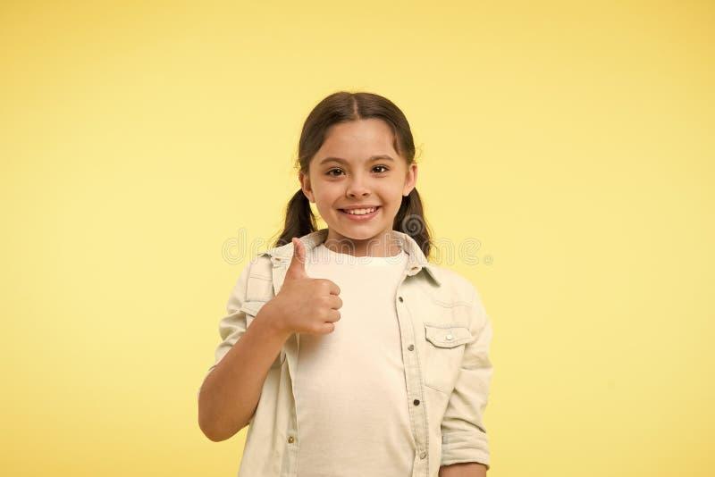 Goede kwaliteit Het jong geitjemeisje toont de duim op gebaar gele achtergrond adviseert Het kind adviseert hoogst met duim op ge stock fotografie