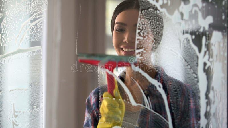 Goede vrouw met genoegen schoonmakend huis en wassende ruimtevensters, orde thuis stock foto