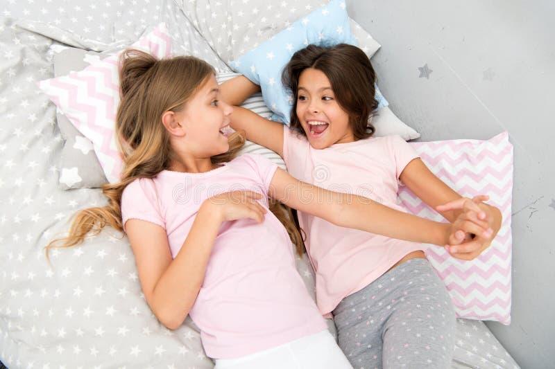 Goedemorgen en gezonde slaap de meisjes zeggen goedemorgen aan elkaar meisjes in bed na gezonde slaap stock afbeelding