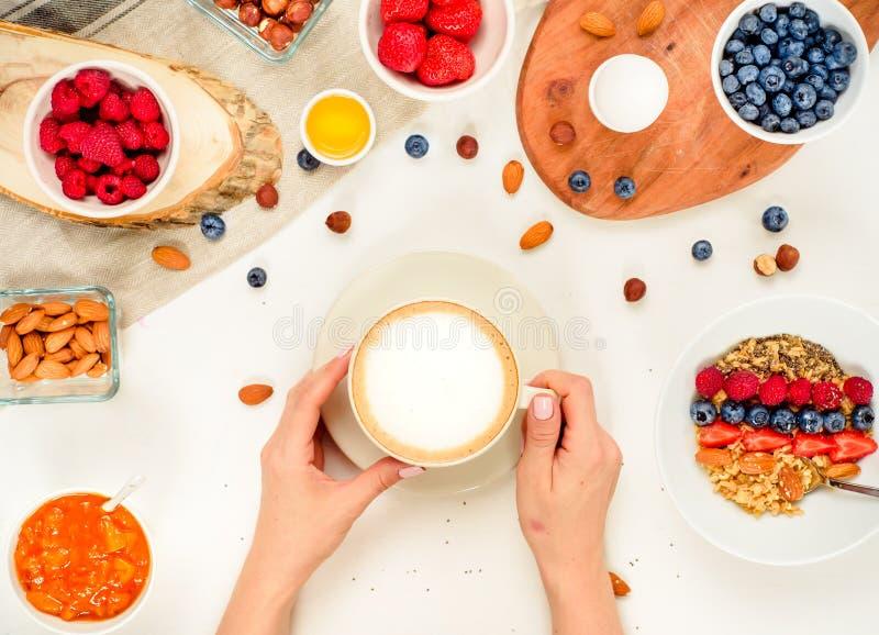Goedemorgen - gezonde ontbijtachtergrond met havermeelkoffie, bessen, ei, noten Koffie, handen, greep, kop Wit houten voedsel B stock foto's
