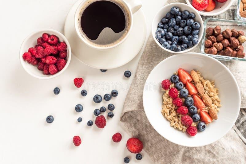 Goedemorgen - gezonde ontbijtachtergrond met havermeelkoffie, bessen, ei, noten Witte houten voedselachtergrond, stock foto's