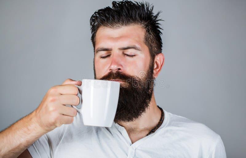 Goedemorgen, mens die een kopthee houden Klok als koffiekop, krant en pen Het knappe gebaarde mannetje houdt kop van koffie, thee royalty-vrije stock fotografie