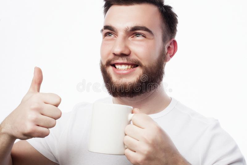 Goedemorgen, mens die een kopthee houden Klok als koffiekop, krant en pen royalty-vrije stock foto's