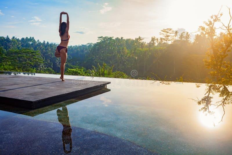 Goedemorgen met vrouwenyoga die op zonsopgangachtergrond mediteren stock foto