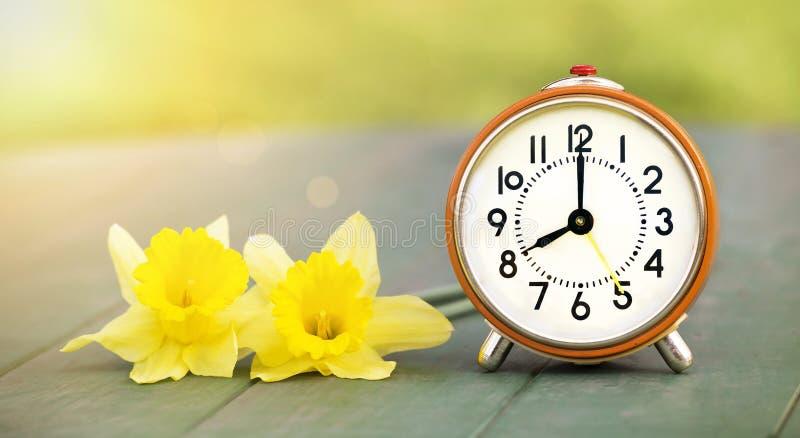 Goedemorgenconcept - bloemen en wekker stock afbeeldingen