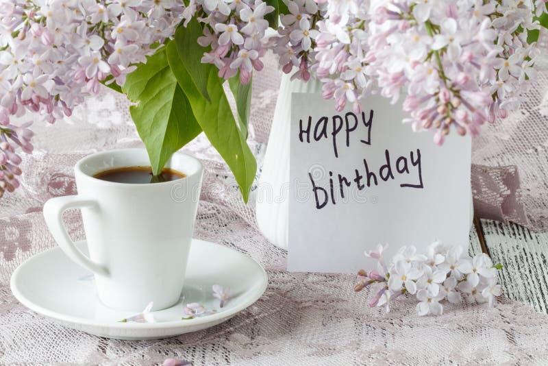 Goedemorgennota, koffiekop en liliac bloemen stock foto
