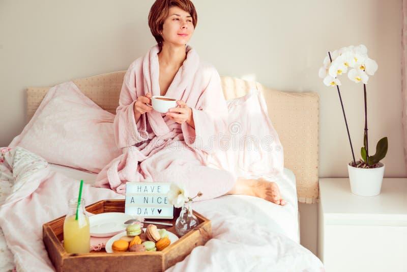 Goedemorgenstemming De jonge vrouw in badjaszitting op het bed, het drinken koffie en heeft haar ontbijt in bed met een aardige d stock foto