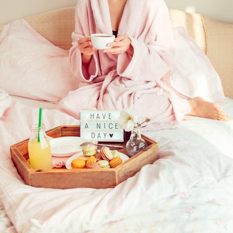 Goedemorgenstemming Geen gezichtsvrouw in badjaszitting op het bed met koffie en heeft ontbijt in bed met een aardige dagtekst he royalty-vrije stock afbeeldingen