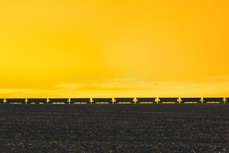 Goederentrein die op de horizon van gebied in het Amerikaanse platteland overgaan Zonsonderganglicht en de stormachtige hemel stock afbeelding