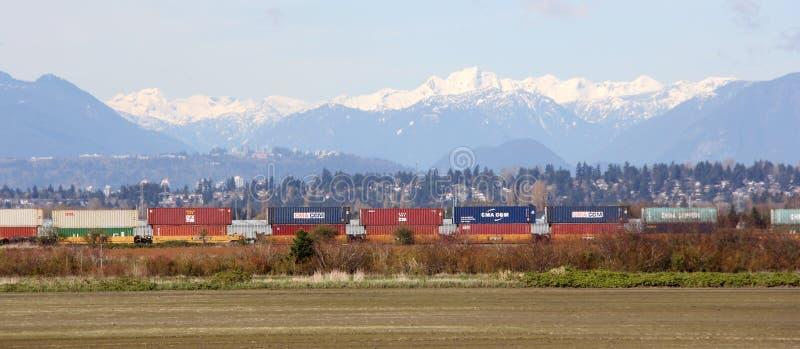 Goederentrein die Toneelbergachtergrond overgaan tot Vancouver, BC royalty-vrije stock foto