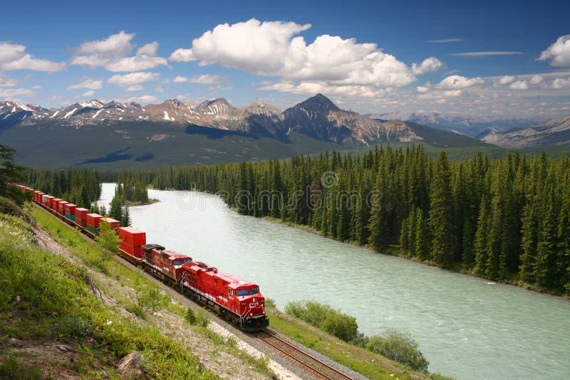 Goederentrein die zich langs de rivier van de Boog in Canadees R beweegt royalty-vrije stock fotografie