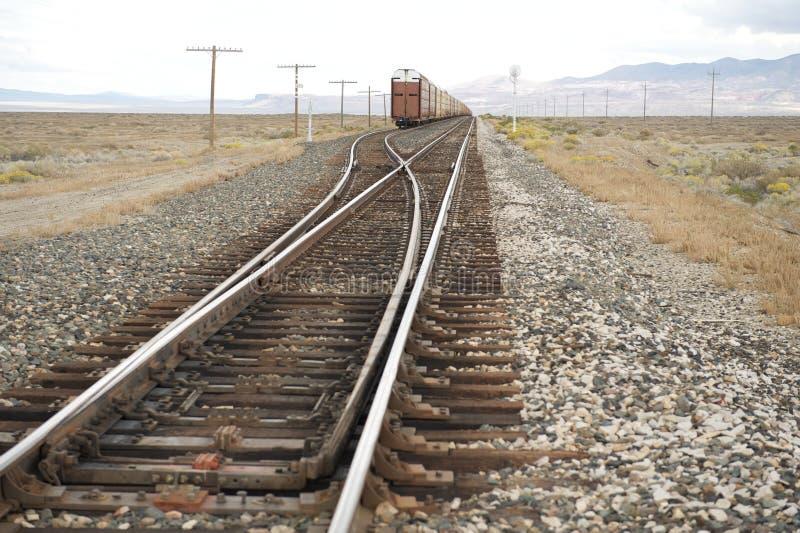 Goederentrein op sporen die woestijn, NV, de V.S. kruisen stock afbeelding
