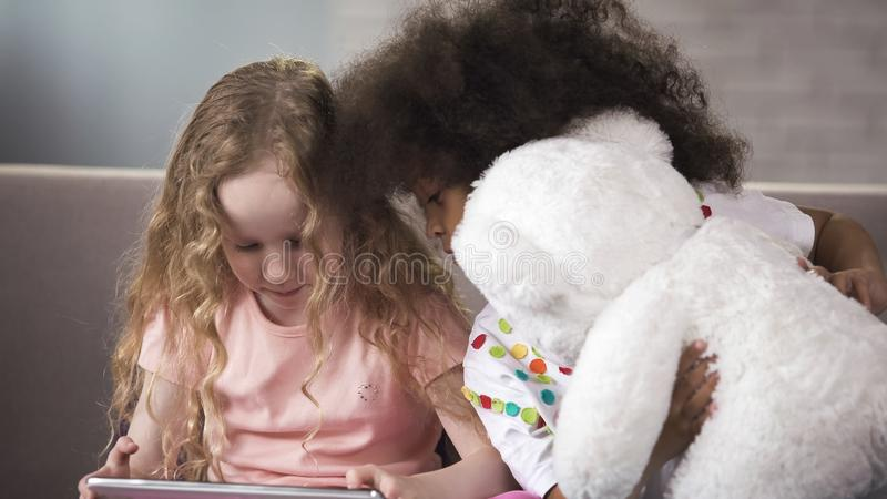 Goedgekeurd Afrikaans jong geitje die teddybeer koesteren, die dichtbij haar lusje van de vriendenholding zitten royalty-vrije stock foto's