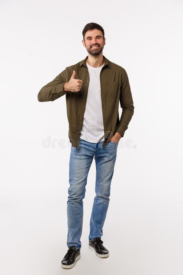 Goedkeuring, aanvaarding en advies Verticaal geschoten, heel lang aantrekkelijke, moderne mannenbebaarde man in jeans stock afbeelding