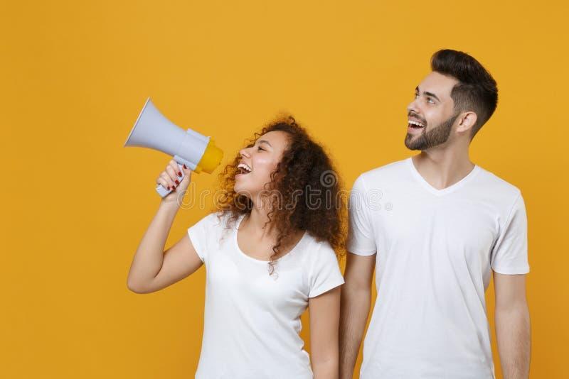 Goedzinnig paar twee vrienden europese kerel afrikaans - amerikaans meisje in witte t-shirts die geïsoleerd zijn op gele achtergr royalty-vrije stock afbeeldingen