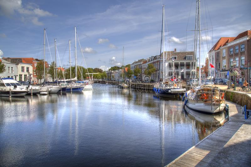 Old harbor of Goes in the Netherlands. Goes, The Netherlands - August 24, 2017: Recreational sailboats lie moored and people sit on benches in the old harbor of stock image